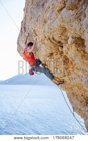 Young man lead climbing on overhanging cliff over sea