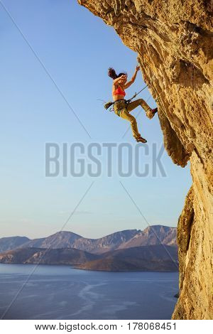 Female rock climber falling off cliff while lead climbing chipped off piece of cliff falling near woman's foot