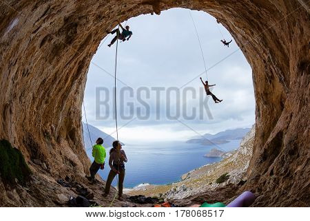 Rock climbers in cave: belayers watching leading climbers two climbers swinging on ropes or being lowered down one male gripping handhold on cliff and looking down