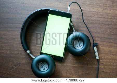On the table headphones, smartphone with green screen for key chroma screen.