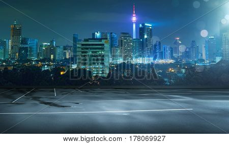 Empty wet asphalt road and cityscape skyline at night with light flare bokeh effect .