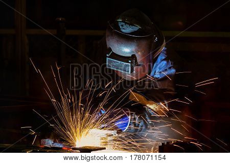 Worker is welding assembly  steel part in factory