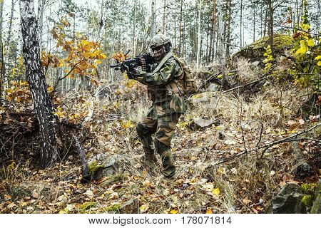 Norwegian Rapid reaction special forces FSK soldier patrolling in the forest. Field camo uniforms, knee pads, combat helmet and eye-wear goggles are on