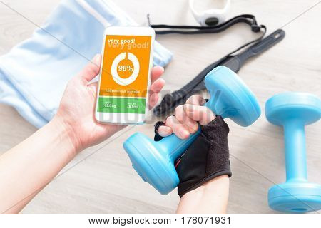 Mobile phone with sport mobile application on screen dumbbels and other sport equipment on a desk