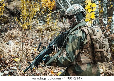 Norwegian Rapid reaction special forces FSK soldier patrolling in the forest. Field camo uniforms, combat helmet and eye-wear goggles are on
