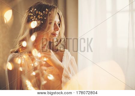 Young lovely housewife with a garland. Girl in sexy gown. Good morning. Dreamy face. Soft focus. Toning.
