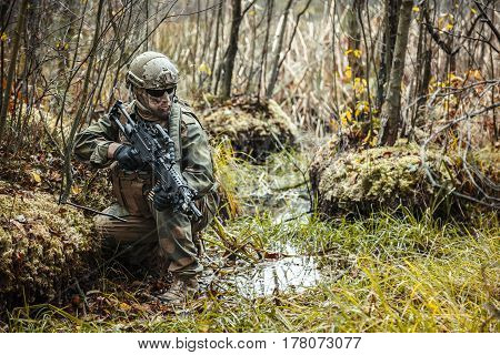 Norwegian Rapid reaction special forces FSK soldier sitting on the swamp. Field camo uniforms, combat helmet and eye-wear goggles are on