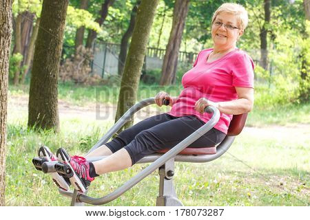 Senior Woman Exercising Upper And Lower Body On Outdoor Gym, Healthy Lifestyle