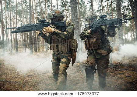 Norwegian Rapid reaction special forces FSK soldiers in field uniforms in action in the forest fog covering each other
