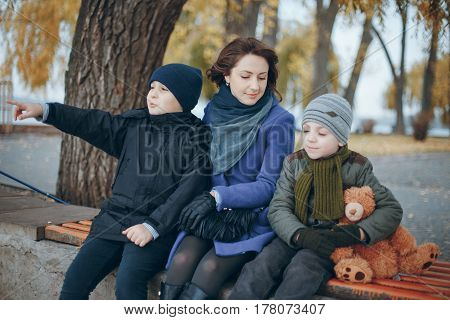 two brothers with mom sitting on a park bench