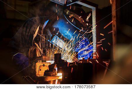 Welder is welding steel with protective mask  in factory