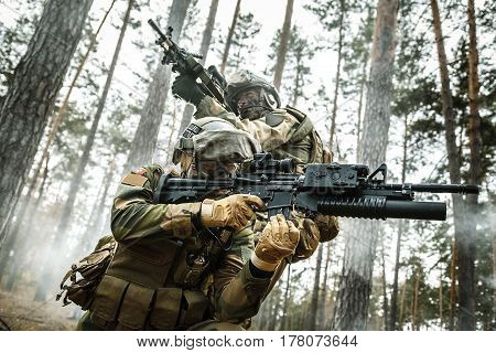 Norwegian Rapid reaction special forces FSK soldiers in field uniforms in action in the forest fog covering each other. Low angle view