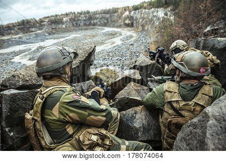 Patrol of norwegian Rapid reaction special forces FSK soldiers in field uniforms in ambush among the rocks guarding perimeter waiting enemy