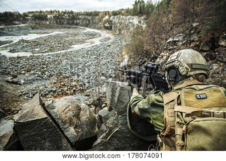 Norwegian Rapid reaction special forces FSK soldier in field uniforms in ambush among the rocks guarding perimeter waiting enemy