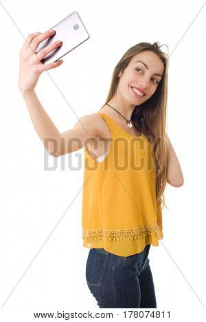 Beautiful woman smiling and taking a selfie, isolated over a white background