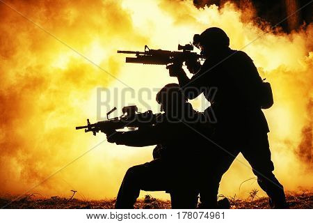 Black silhouettes of pair of soldiers in the smoke fire burning moving in battle operation. Back light