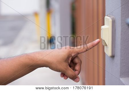 The man press the bell button in front of the house.