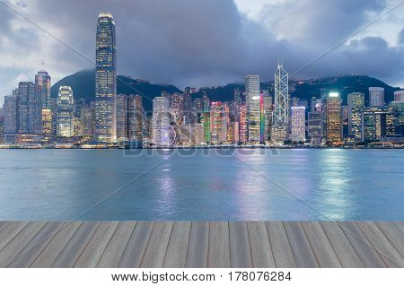 Opening wooden floor Hong kong office building at twilight sea front cityscape background