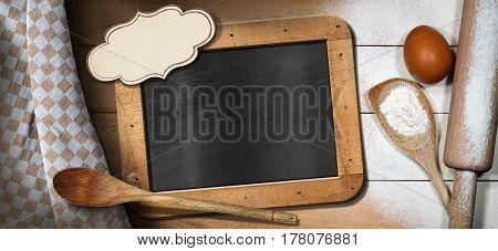 Baking background with empty blackboard and label on a wooden table with flour egg rolling pin spoons and brown and white checkered tablecloth