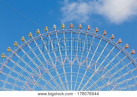 Big funfair festival ferris wheel against blue sky background