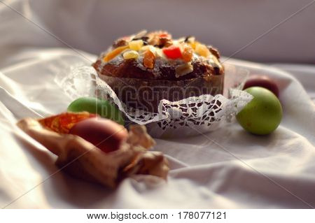 Sweet Easter cake with dried fruits on a snow-white openwork napkin and dyed eggs / the Easter cake and dyed eggs