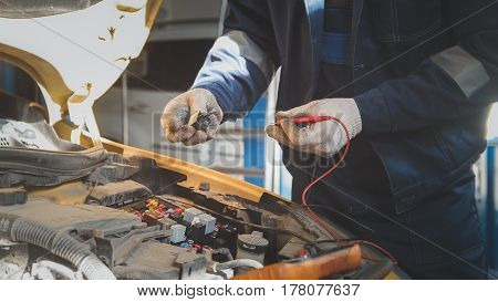 Mechanic in auto workshop works with car electrics - electrical wiring, voltmeter, close up