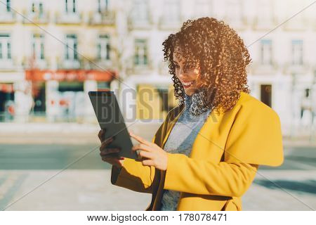 Beautiful curly smiling Brazilian woman in yellow coat and sweater having video call using digital tablet adult attractive laughing lady making selfie on touch pad while standing on sunny street