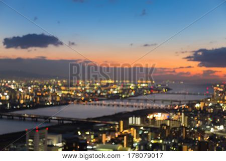 Aerial view blurred bokeh light Osaka city with sunset sky abstract background