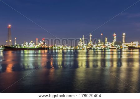 Night blurred light Oil refinery with water reflection abstract background