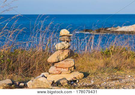 Stack rock over coastline with blue ocean skyline background