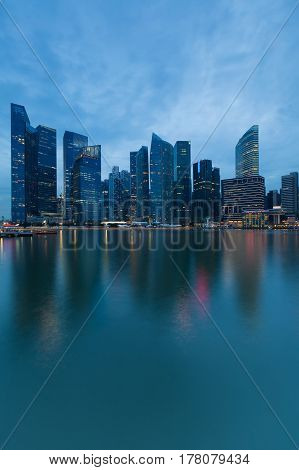 Twilight Singapore city office building downtown water front and reflection cityscape downtown background