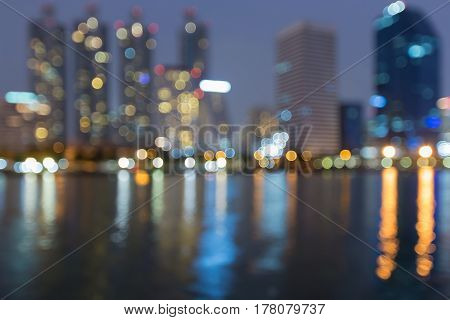 Twilight blurred bokeh city office building with water reflection abstract background
