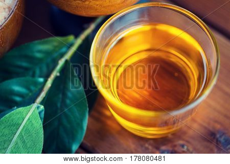 beauty, spa, body care, natural cosmetics and wellness concept - close up of honey in glass cup with leaves on wooden table