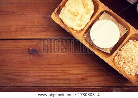 beauty, spa, body care, natural cosmetics and wellness concept - close up of soap with himalayan pink salt and scrub in wooden bowl on table