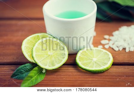beauty, spa, body care, natural cosmetics and wellness concept - close up of citrus body lotion in cup and sea salt with limes on wooden table