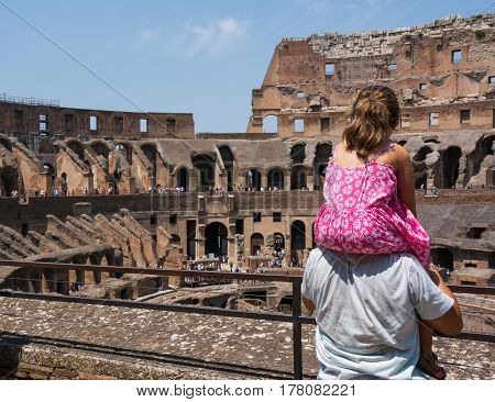 ROME, ITALY - JULY 17, 2015: Father is holding his daughter on his shoulders to see the inside arena of Coliseum on a sunny hot summer day. Family observing ancient construction of Colloseo a famous historic site and a popular tourist destination