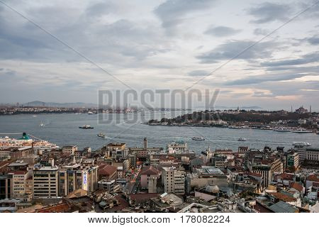 Scenic view with clouds on sunset sky over Bosporus with touristic ships and buildings in the foreground in Istanbul Turkey