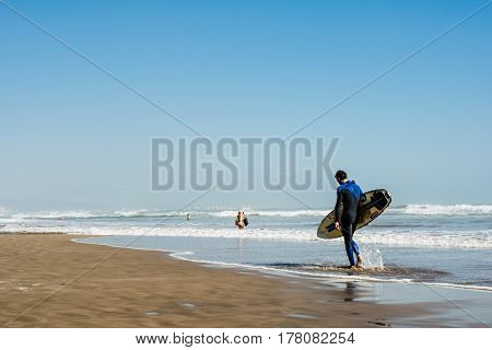 VALENCIA, SPAIN - OCTOBER 1, 2015: Professional male surfer in black and blue diving suit carrying his surfboard while walking along the shore of a sand beach in Valencia in the end of season