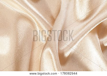 Silk background texture of beige shiny fabric close up