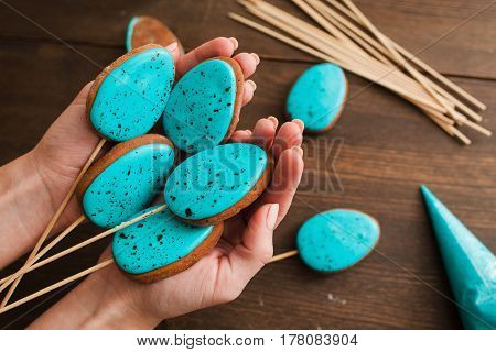 Homemade easter cake pops with blue icing on rustic wooden table top view
