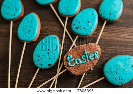 Blue iced cake pops on the wood background for easter celebration, top view. Holiday sweets concept