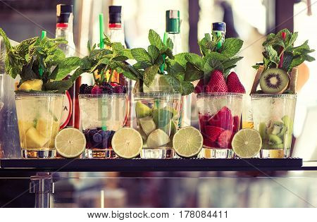 Five glasses of mojito with fruits and mint. Fruit Alcoholic Cocktails
