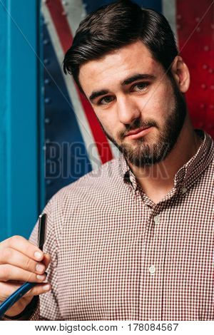 Young attractive man with straight razor. Portrait of beautiful brunet holding cutthroat in hand. Barbershop, shaving, grooming concept