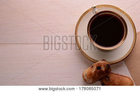 On a wooden table on the right is a demitasse with a gold rim. Near the coffee cup is homemade shortbread with chocolate.