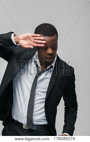 Black afroamerican guy on grey background. Closed face, rejection, separated, reluctance to see, indifference, ignorance