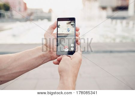 Ukraine, Kharkiv - 10 August, 2016: Pokemon Go playing game on mobile phone with blurred background closeup. Catch a Pokemon in real world.