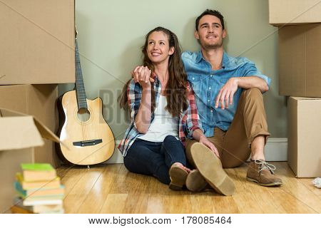 Young couple sitting together on the floor and smiling in their new hous