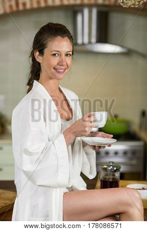 Portrait of beautiful woman in bathrobe sitting on kitchen worktop and having a cup of tea