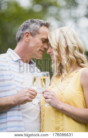 Happy couple drinking champagne outside