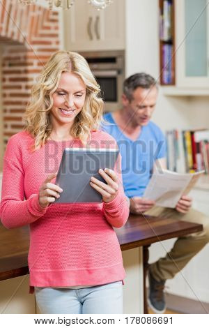 Happy wife using tablet while husband reading newspaper in the kitchen